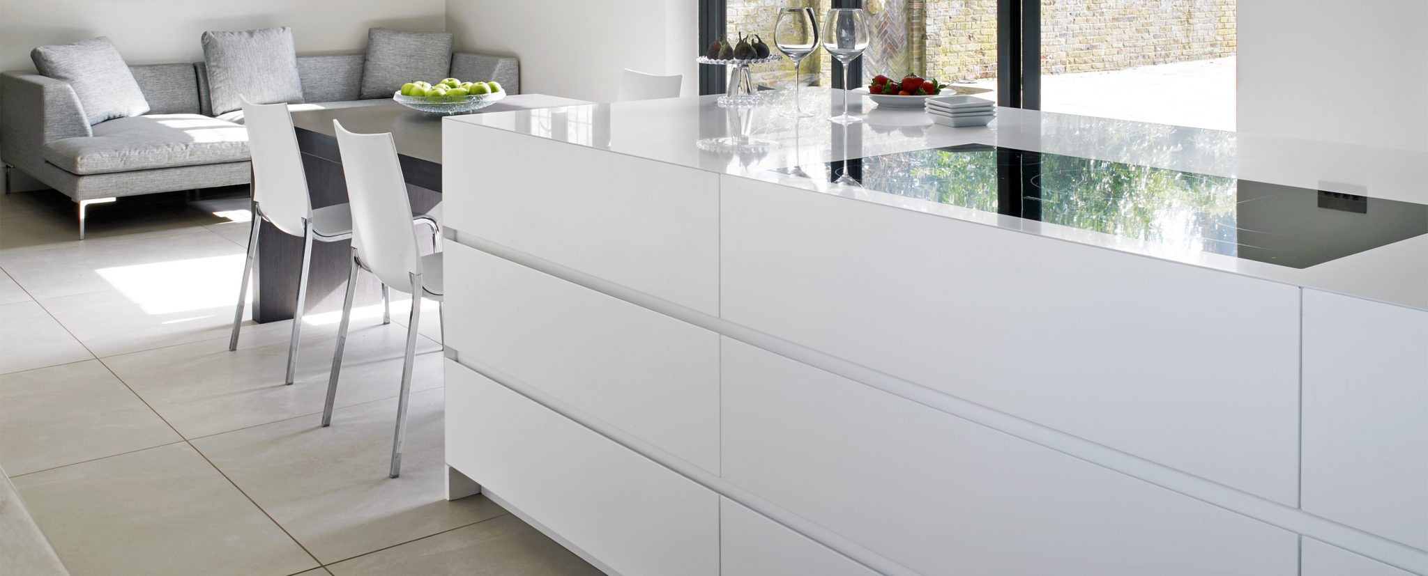 White Contemporary kitchen island with integrated induction hob and attached dining table