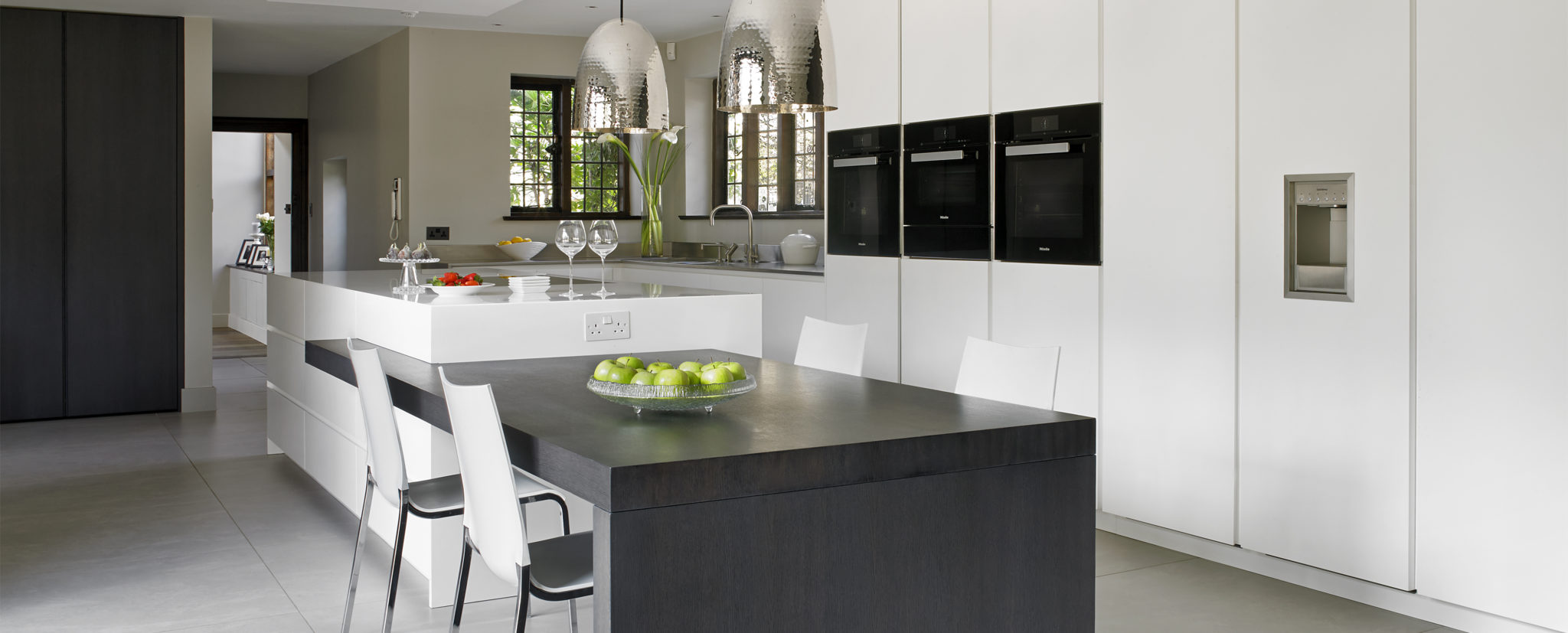White modern kitchen design featuring island with attached dining table