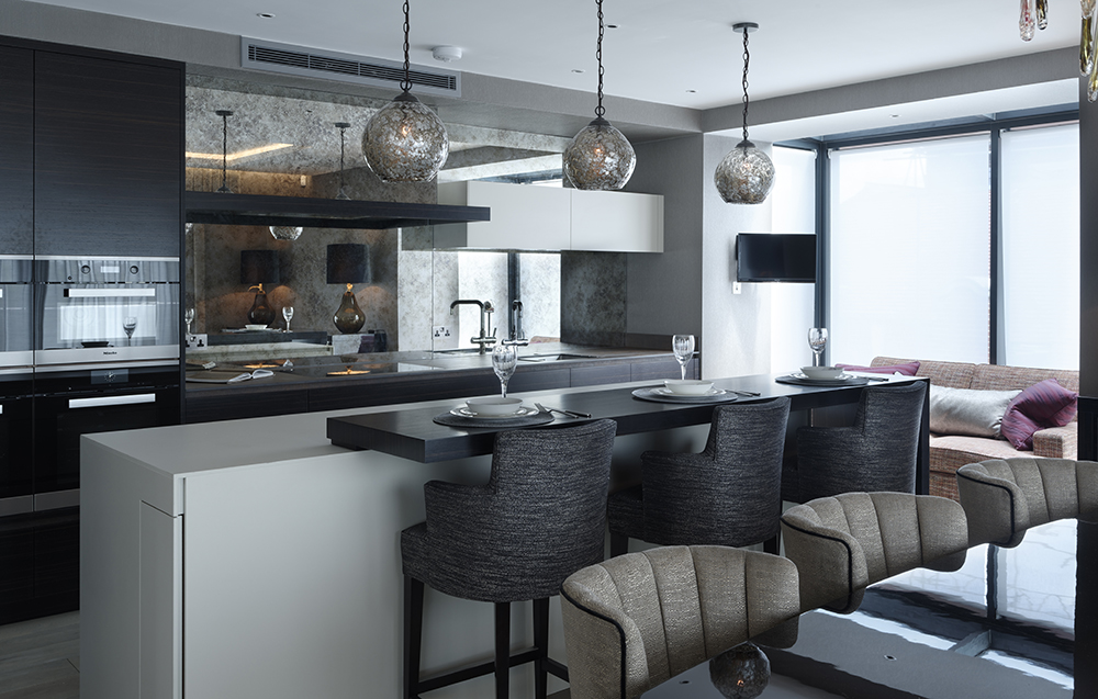 Luxury Chelsea kitchen design with breakfast bar and mirrored splashback, glitterball pendant lights and integrated appliances