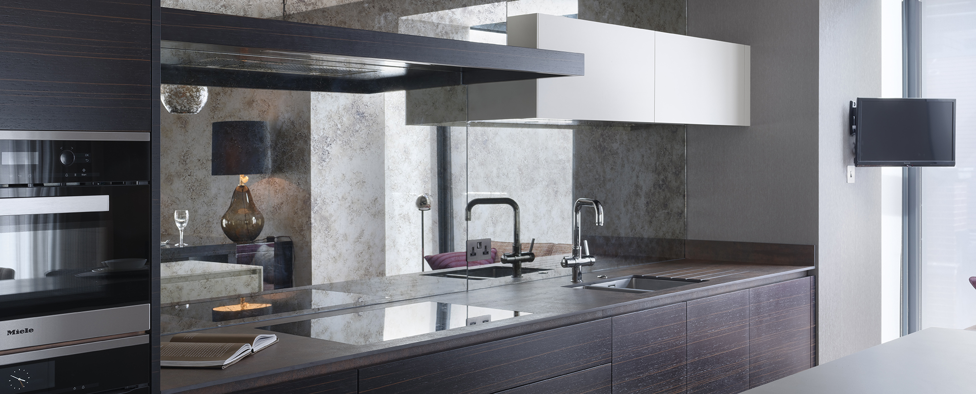 Kitchen design for Chelsea apartment with mirror splashback and modern handleless cabinets