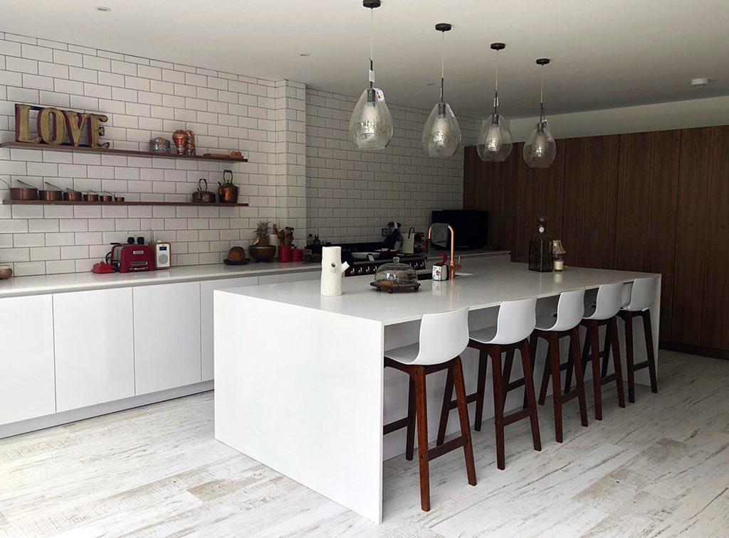 Simple white modern kitchen with Walnut accents, metro tiled wall and large island with breakfast bar