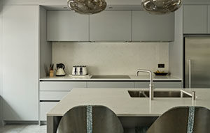 Grey kitchen design for Wimbledon home renovation - modern kitchen island with breakfast bar and integrated sink, flat panel handleless kitchen cabinets in warm grey matt lacquer with flush mounted hob and composite splashback.