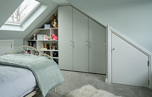 Custom fitted wardrobes and display cabinet for loft bedroom in light grey - girl's bedroom.