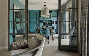 View from sitting room through crittall doors of oriental-style dining room with turquoise and dark wood display cabinet.