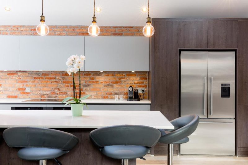 Modern non bespoke kitchen by Brayer Design featuring exposed brick wall, island and breakfast bar with pendant lighting and flat, handleless kitchen cabinets in a minimalist style.