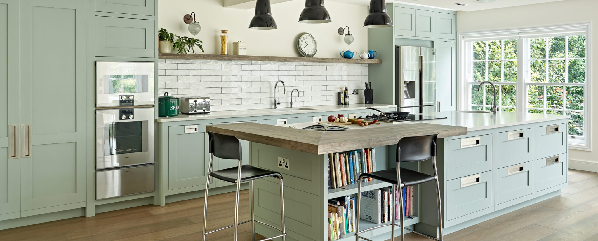 Pale green modern shaker style kitchen renovation with large island, wall mounted ovens, breakfast cupboard and metro tile splashblack