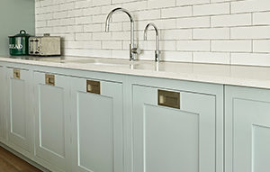 Modern shaker kitchen cabinets in pale green shade with rectangular recessed handles in brushed stainless steel. Submerged sink with Quooker tap and white tile splashback.