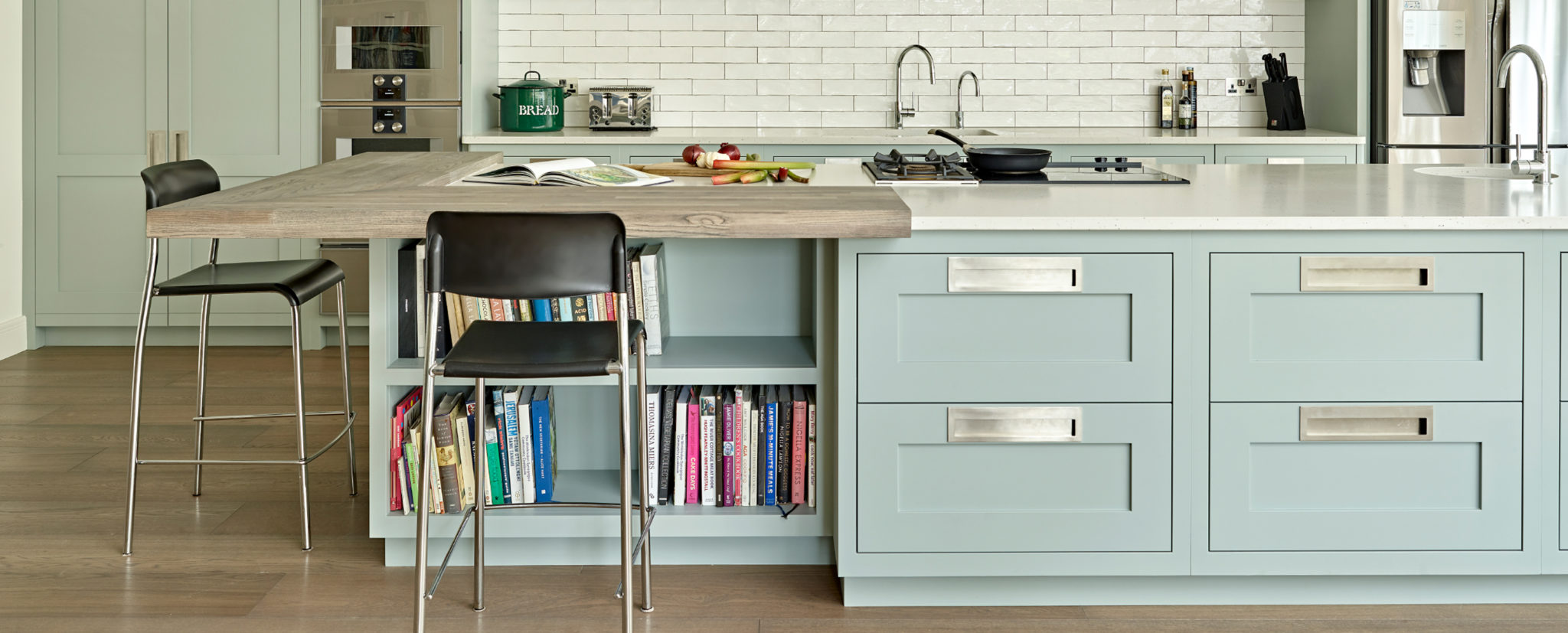 Pale Green Kitchen Island with large rectangular handles in brushed stainless steel with built in bookcase and elevated breakfast bar in Prima Heart Ash.
