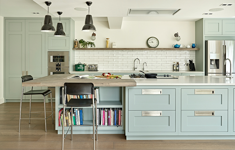 Modern shaker kitchen design with pale green cabinets and brushed stainless steel handles with large island and open shelves.