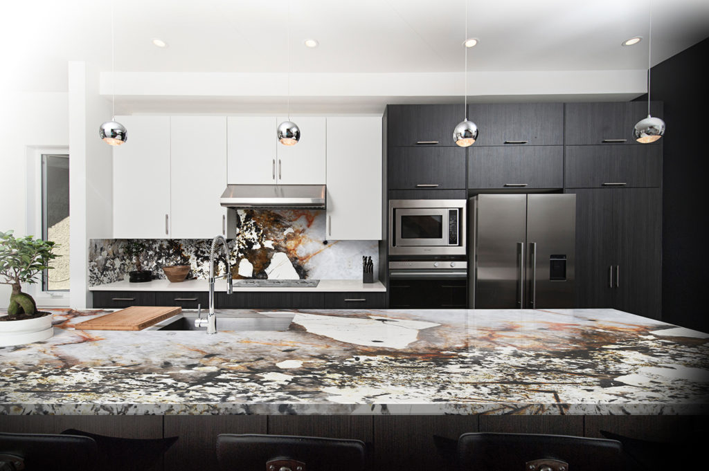 Neutral earthy tones of Patagonia granite worktops and splashback in contemporary kitchen design
