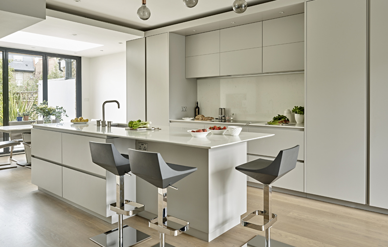 Minimalist kitchen design with handleless grey matt lacquer cabinets and Bianco Massa worksurfaces with shark nose edge - Contemporary Wimbledon Kitchen