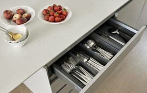 Kitchen island cutlery drawer with dark grey interior and light grey exterior. Bianco Massa 20mm island worktop.