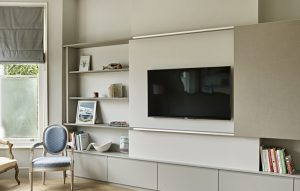 Built-in bespoke media wall and display shelving for Wimbledon home renovation with slide-to-hide TV panel.