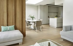 View from lounge looking towards dining and kitchen area of this grey and light oak minimalist open plan kitchen design.