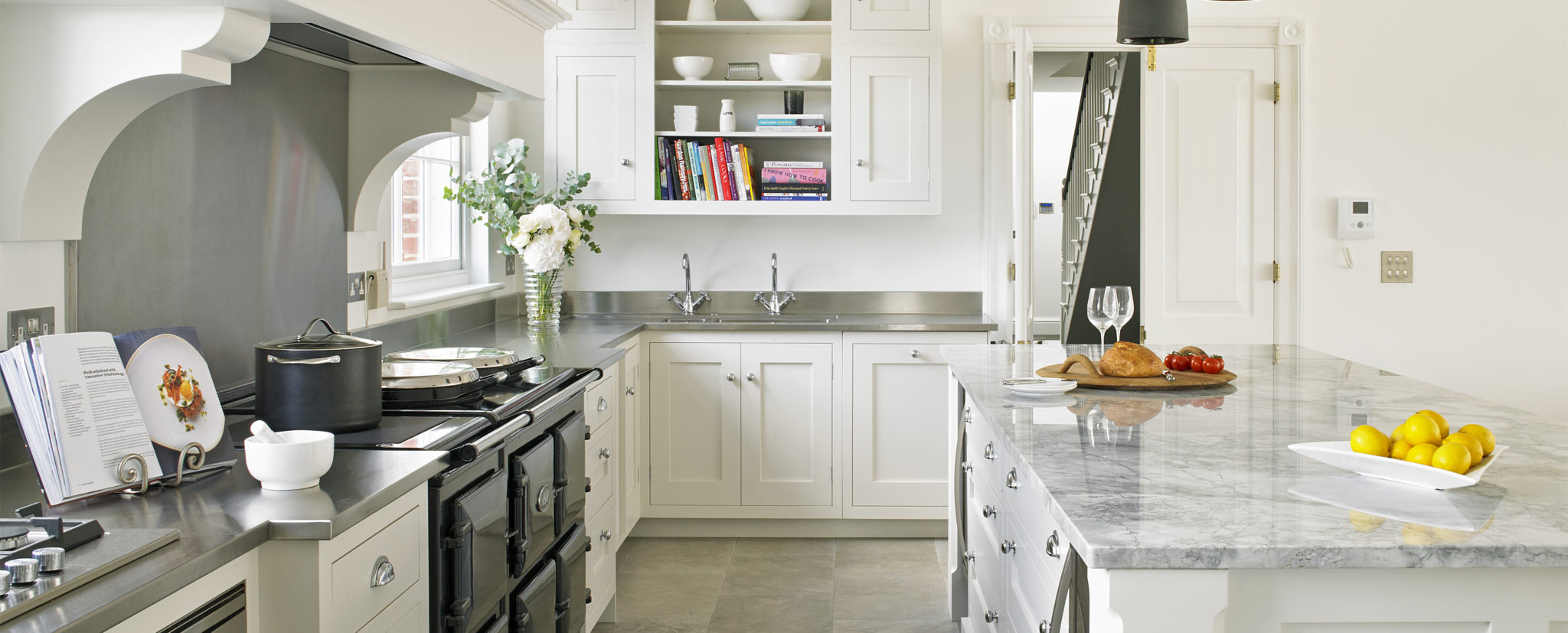 Modern white country style kitchen with AGA range cooker in chimney alcove with extractor, stainless steel and super white quartzite worktops. Strong white shaker kitchen cabinets with traditional cup handles and pulls in polished chrome.