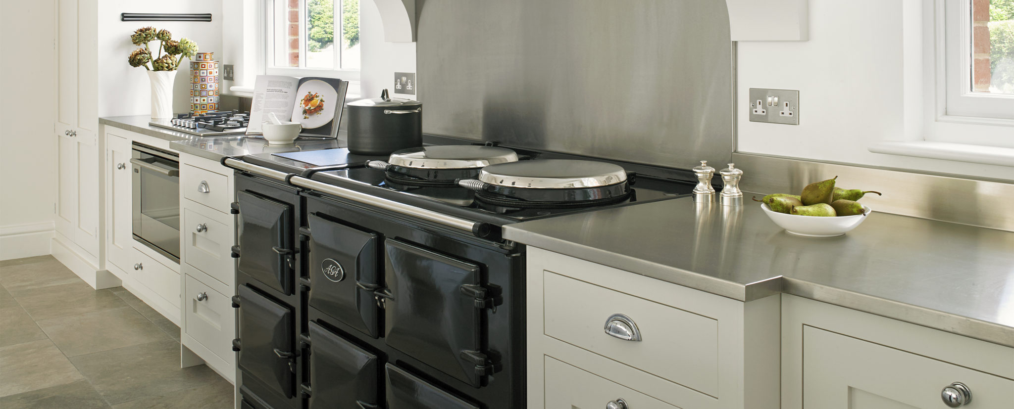 Country range black AGA - white country kitchen design with stainless steel worktops and cup handles