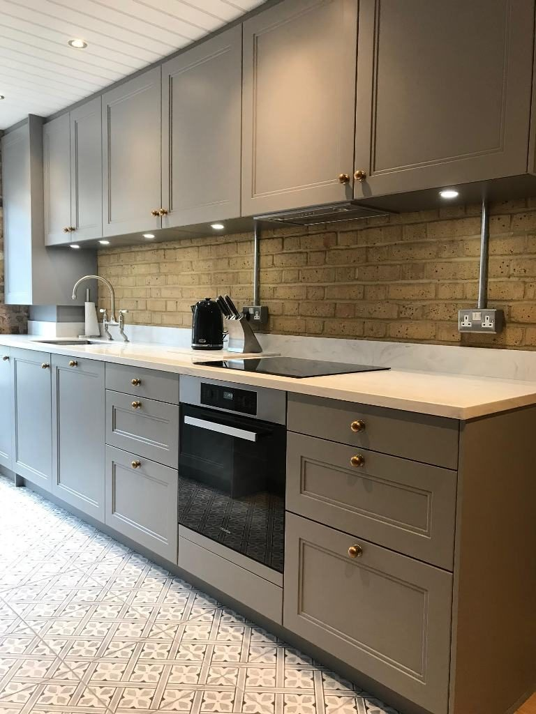 Kitchen Design from the non-bespoke shaker kitchen range by Brayer Design with grey cabinets, exposed brick wall, brass hardware, patterned floor tiles by Laura Ashley and Miele oven.
