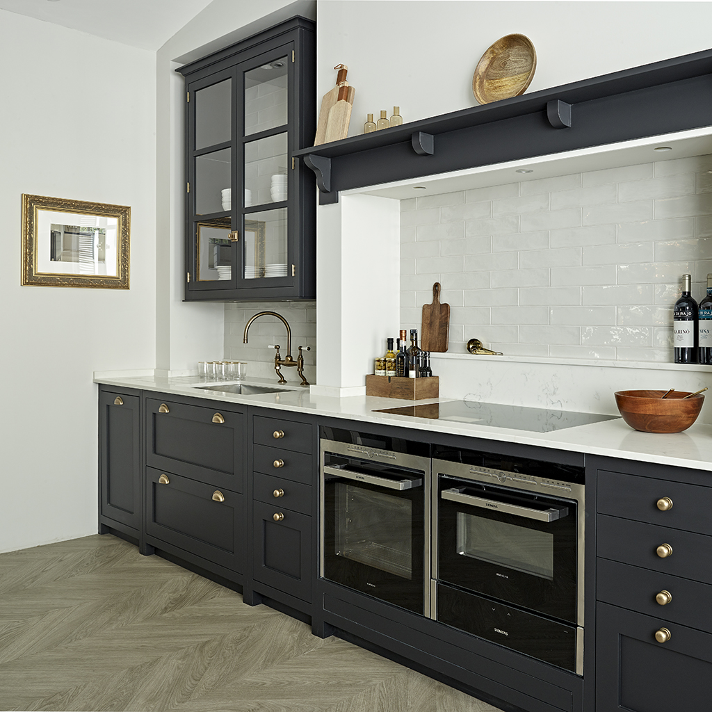 Dark blue shaker kitchen design with brass handles and white tile splashback