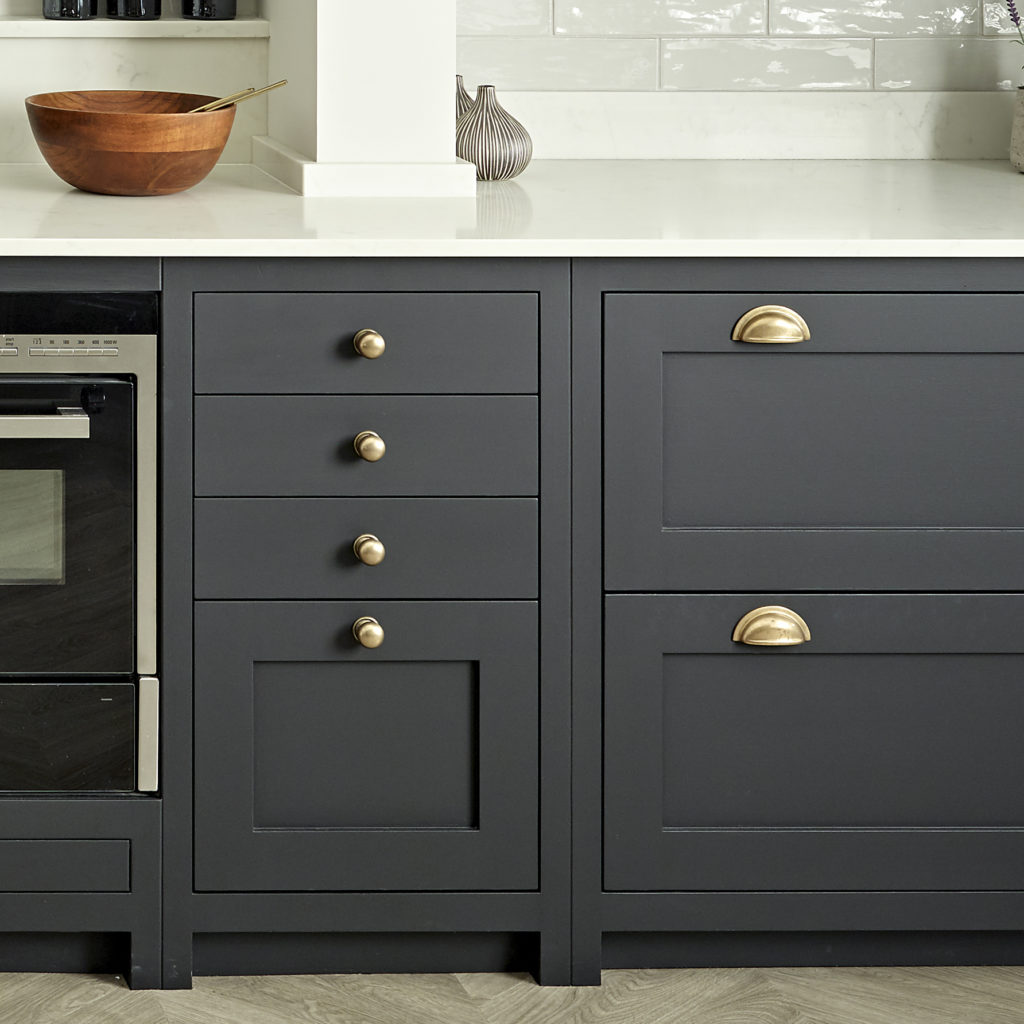 Brassware handles and hinges in burnished brass for dark blue-black kitchen cabinets