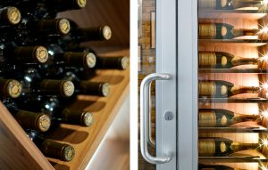 Glass champagne display wall for wine room entrance with presentation lighting and bespoke wooden wine racks.