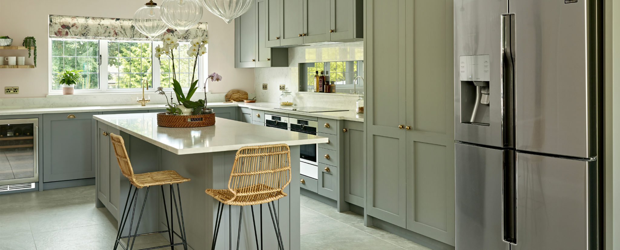 Kingwood kitchen design with island and pantry cabinet. Lead grey cabinets with brass hardware. Pale pink walls, white quartz worktops and stainless steel appliances.