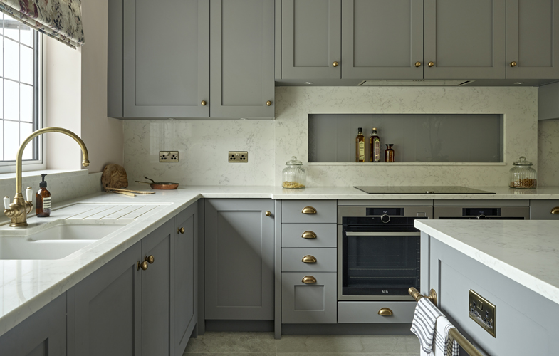 Kingswood kitchen design with grey shaker cabinets, white composite worktops and burnished brass hardware