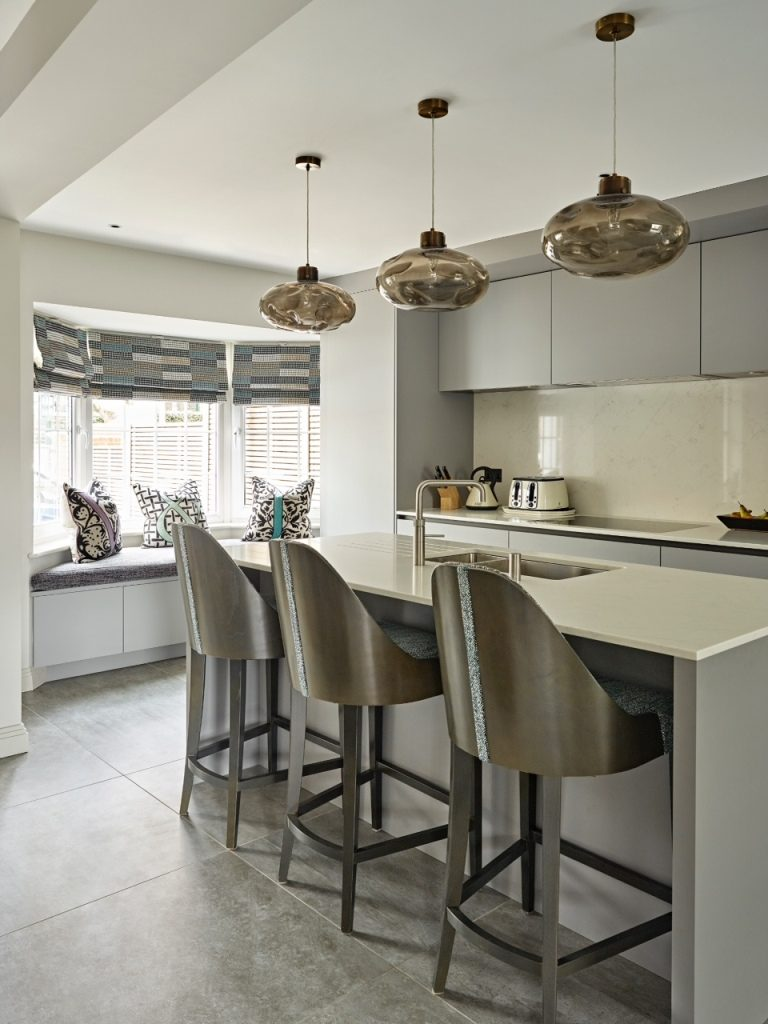 Grey modern handleless kitchen with island and window seat