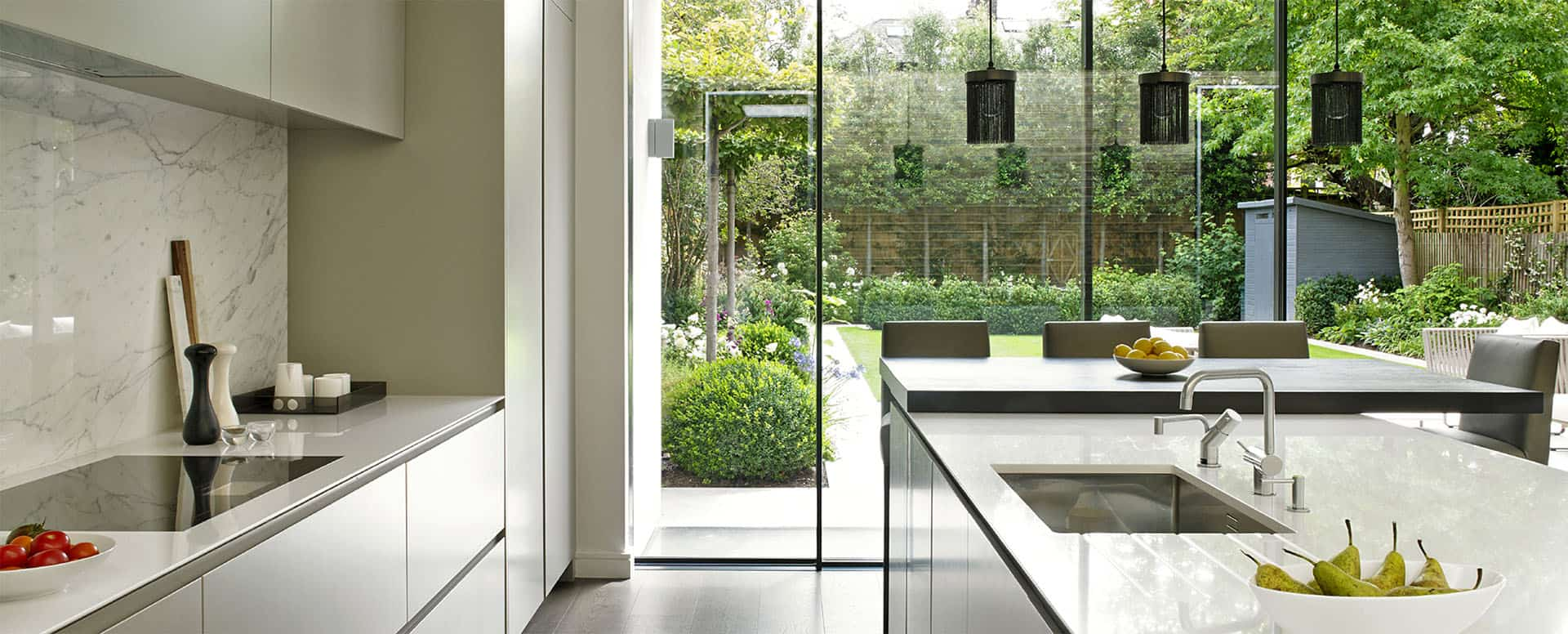Grey modern Kitchen design, Wandsworth - minimalist, handleless kitchen cabinets and induction hob, island with sink, breakfast bar and sliding glass doors leading out into garden