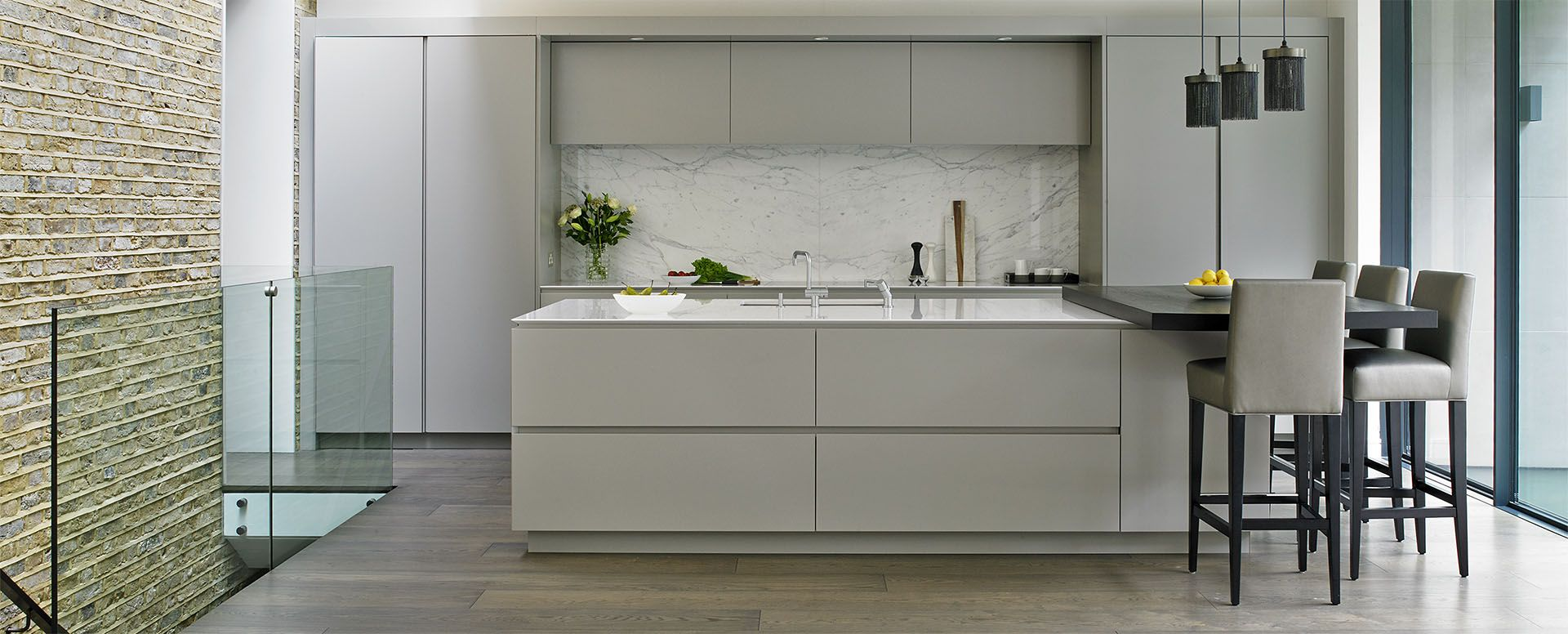 Grey Modern Kitchen with Sleek Handleless cabinets and island with elevated breakfast bar in Wandsworth