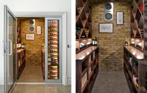 Wine room with bare brick wall and champagne display case at entrance. Bespoke wooden wine racks and display cabinets with lighting. Temperature controlled and with built-in speaker system